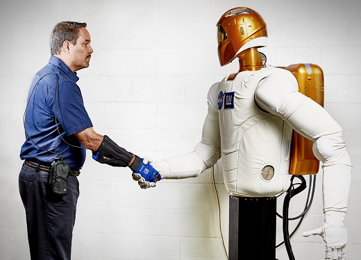 Handshake - Marty Linn, General Motors manager of advanced technology and principal engineer for robotics, shakes hands with Robonaut 2 (R2), a humanoid robot developed by GM and NASA during a nine-year collaboration that also led to development of the RoboGlove, an exo-muscular device that enhances  strength and grip through leading-edge sensors, actuators and tendons that are comparable to the nerves, muscles and tendons in a human hand. GM is licensing the RoboGlove intellectual property to Bioservo Technologies AB, a Swedish medical technologies company that will combine RoboGlove with its owner patented SEM glove technology.